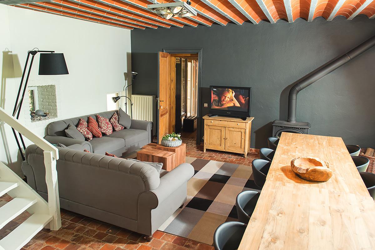 salon en eethoek met houtkachel in rustiek vakantiehuis