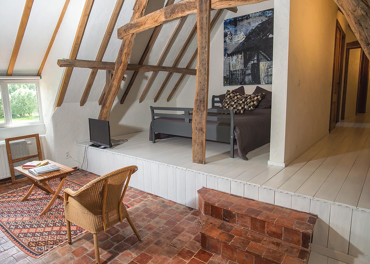 slaapkamer met leeshoek met authentieke elementen in hout en steen